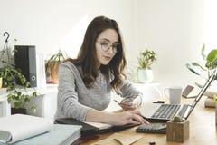 Junge Geschäftsfrau, die Geld im Büro zählt stockbilder