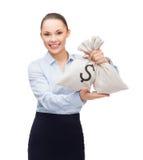 Junge Geschäftsfrau, die Geldtaschen mit Dollar hält Stockbilder