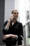 Junge Geschäftsfrau, die am Handy spricht Stockbilder