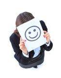 junge Geschäftsfrau, die hinter einem smileygesicht sich versteckt Stockfotos