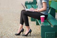 Junge Geschäftsfrau, die an ihrem Laptop arbeitet Lizenzfreie Stockfotos