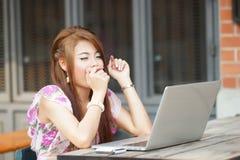 Junge Geschäftsfrau, die an ihrem Laptop am Freiencafé, sie arbeitet Stockfotografie