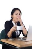 Junge Geschäftsfrau, die an ihrem Schreibtisch mit einem Tasse Kaffee gähnt Lizenzfreie Stockfotografie