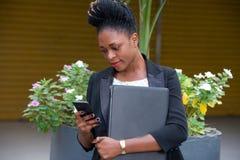 Junge Geschäftsfrau, die ihren Handy mit Aufmerksamkeit betrachtet lizenzfreie stockbilder
