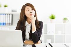 Junge Geschäftsfrau, die im Büro denkt Stockfotografie