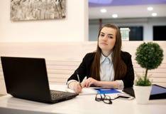 Junge Geschäftsfrau, die im Büro mit einem Laptop arbeitet Lizenzfreie Stockfotografie