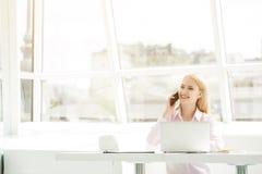Junge Geschäftsfrau, die im Büro sitzt Lizenzfreie Stockfotos