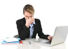 Junge Geschäftsfrau, die im Druck und in den Kopfschmerzen am Bürocomputer frustriert arbeitet stockfotografie