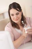 Junge Geschäftsfrau, die Joghurt im Büro isst Stockfotos