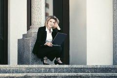 Junge Geschäftsfrau, die Laptop auf den Schritten verwendet Lizenzfreie Stockfotografie