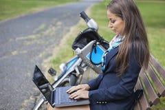 Junge Geschäftsfrau, die Laptop beim Sitzen auf Bank am Park verwendet Stockbild