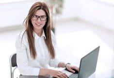 Junge Geschäftsfrau, die Laptop an dem Arbeitsplatz verwendet lizenzfreies stockbild