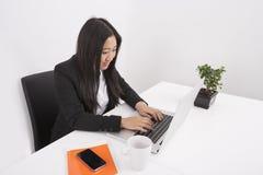 Junge Geschäftsfrau, die an Laptop am Schreibtisch arbeitet Lizenzfreie Stockfotografie