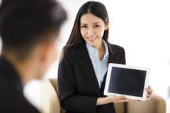 Junge Geschäftsfrau, die leere Tablette im Büro zeigt stockfotografie