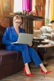 Junge Geschäftsfrau, die on-line-Sitzen auf Sofa bearbeitet lizenzfreies stockfoto