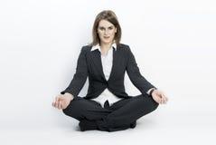Junge Geschäftsfrau, die in Lotosstellung sitzt. Stockbilder