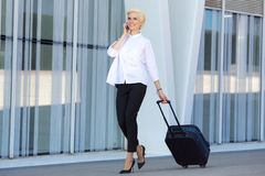 Junge Geschäftsfrau, die mit Koffer geht Lizenzfreies Stockbild