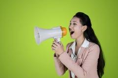 Junge Geschäftsfrau, die mit Megaphon spricht stockbild