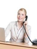 Junge Geschäftsfrau, die mit Telefonhörer sitzt stockfotos