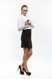 Junge Geschäftsfrau, die Mitteilung auf Mobiltelefon schaut Lizenzfreies Stockbild