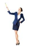 Junge Geschäftsfrau, die oben mit Stift zeigt. Stockbilder