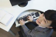 Junge Geschäftsfrau, die am Schreibtisch, schauend oben sitzt lächelnd Lizenzfreies Stockfoto