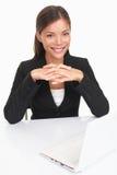 Junge Geschäftsfrau, die am Schreibtisch sitzt Stockfotos