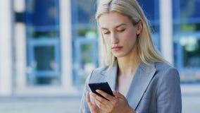 Junge Geschäftsfrau, die Smartphone nahe Gebäude verwendet stock video footage