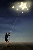 Junge Geschäftsfrau, die Sterne nimmt stockfotografie