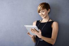 Junge Geschäftsfrau, die Tablette verwendet stockbild