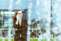 Junge Geschäftsfrau, die am Telefon in Berlin spricht lizenzfreie stockbilder