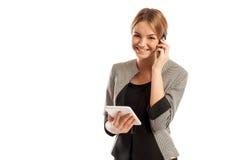 Junge Geschäftsfrau, die am Telefon spricht und Tablette hält Lizenzfreie Stockfotografie