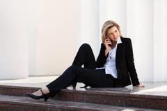 Junge Geschäftsfrau, die um den Handy ersucht Stockfotos