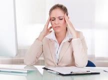 Junge Geschäftsfrau, die unter Kopfschmerzen leidet Stockbild