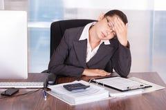 Junge Geschäftsfrau, die unter Kopfschmerzen leidet Lizenzfreies Stockbild