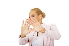 Junge Geschäftsfrau, die versucht, sich zu schützen Lizenzfreies Stockfoto