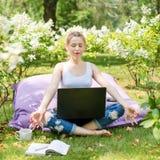 Junge Geschäftsfrau, die Yoga außerhalb des Bürogebäudes sitzt in Lotussitz im Park mit ihrem Laptop und Tasse Tee oder Co tut Lizenzfreies Stockbild