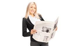 Junge Geschäftsfrau, die Zeitung hält und an der Wand sich lehnt Stockfoto