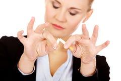 Junge Geschäftsfrau, die Zigarette bricht lizenzfreie stockfotografie