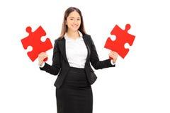 Junge Geschäftsfrau, die zwei Stücke des Puzzlespiels hält Lizenzfreies Stockfoto