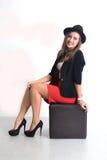 Junge Geschäftsfrau in einem roten Rock und in einer schwarzen Jacke Stockbild