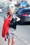 Junge Geschäftsfrau gegen einen Stadtverkehr Lizenzfreie Stockbilder
