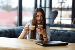 Junge Geschäftsfrau im Restaurant, das Smartphoneschirm betrachtet Trinkender Cappuccino junger Dame lizenzfreies stockbild