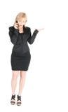 Junge Geschäftsfrau im Schwarzen mit dem smartphone, das über weißem Hintergrund aufwirft Stockfoto