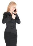 Junge Geschäftsfrau im Schwarzen mit dem smartphone, das über weißem Hintergrund aufwirft Lizenzfreies Stockfoto