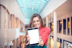Junge Geschäftsfrau ist in der Mitte des eingetragenen Warenzeichens und stellt etwas auf Tablet-Computer dar Stockfotografie