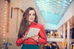 Junge Geschäftsfrau ist in der Mitte des eingetragenen Warenzeichens und stellt etwas auf Tablet-Computer dar Stockbilder