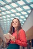 Junge Geschäftsfrau ist in der Mitte des eingetragenen Warenzeichens und stellt etwas auf Tablet-Computer dar Lizenzfreies Stockbild