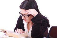 Junge Geschäftsfrau liest das Buch im Büro Stockfotografie