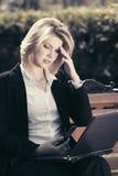 Junge Geschäftsfrau mit dem Laptop, der auf einer Bank sitzt Stockbilder